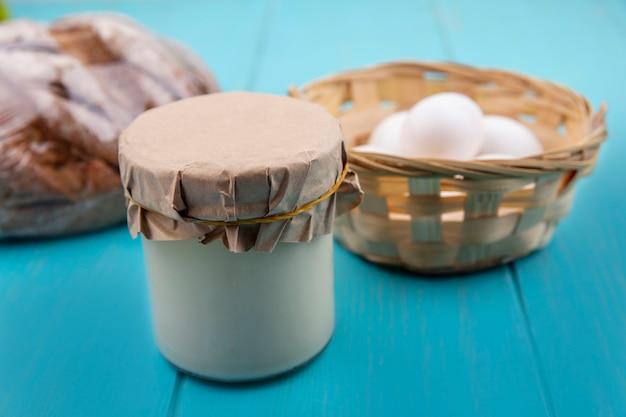 Vista frontal de iogurte em uma jarra com ovos de galinha em uma cesta e pão preto em um fundo turquesa