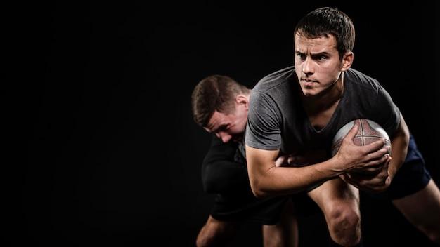 Vista frontal de jogadores de rugby do sexo masculino com bola e espaço de cópia