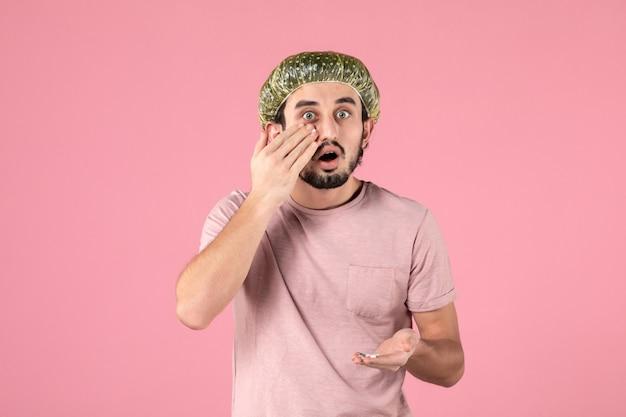 Vista frontal de jovem aplicando máscara em seu rosto na parede rosa