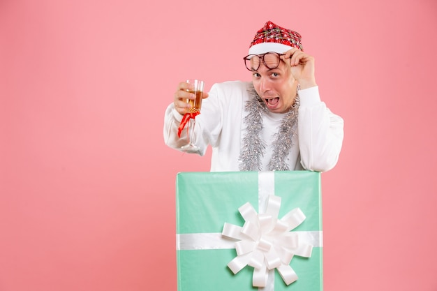 Vista frontal de jovem celebrando o natal com bebida na parede rosa