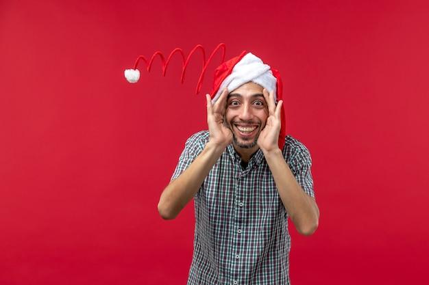 Vista frontal de jovem com boné de brinquedo engraçado na parede vermelha