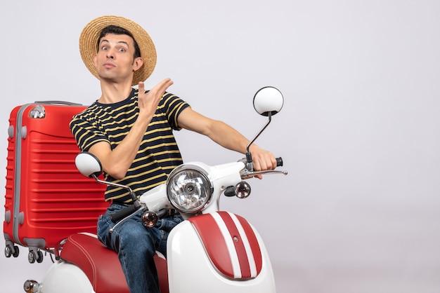 Vista frontal de jovem com chapéu de palha na motocicleta em pé sobre fundo branco