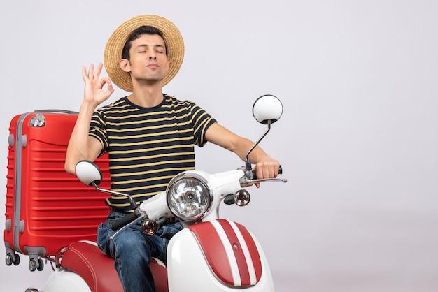 Vista frontal de jovem com chapéu de palha na motocicleta gesticulando sinal de ok fechando os olhos