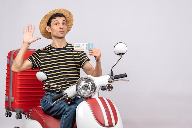 Vista frontal de jovem com chapéu de palha na motocicleta segurando a passagem de avião e acenando com a mão