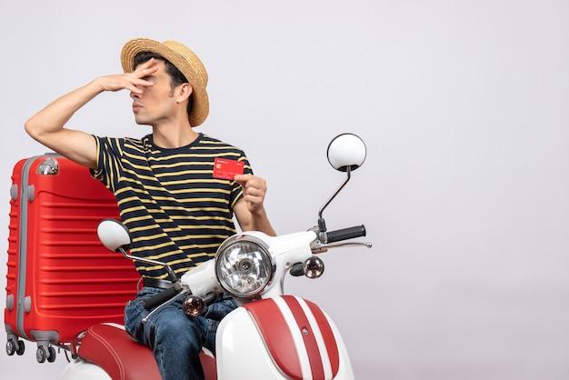 Vista frontal de jovem com chapéu de palha na motocicleta segurando o cartão de crédito e colocando a mão no rosto