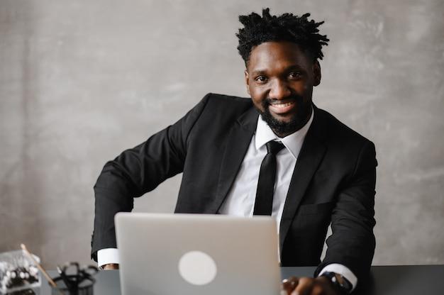 Vista frontal de jovem empresário afro-americano sorridente, olhando para a tela do laptop