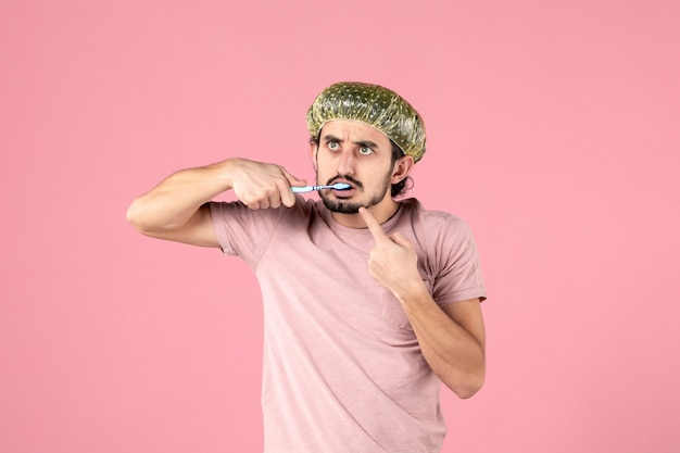 Vista frontal de jovem escovando os dentes na parede rosa