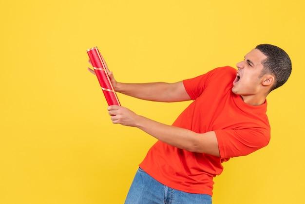 Vista frontal de jovem explodindo foguetes na parede amarela
