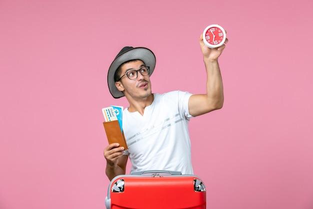 Vista frontal de jovem segurando bilhetes de férias e relógio no piso rosa avião viagem homem foto viagem férias