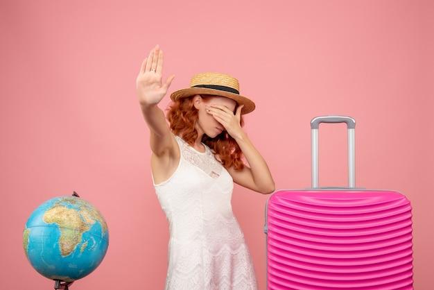 Vista frontal de jovem turista com bolsa rosa na parede rosa