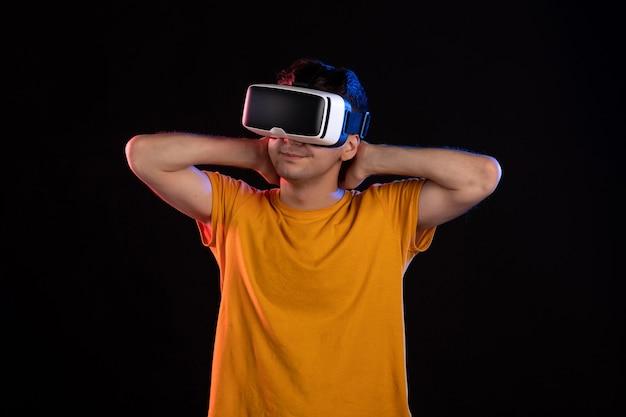 Vista frontal de jovem usando fone de ouvido de realidade virtual na parede escura