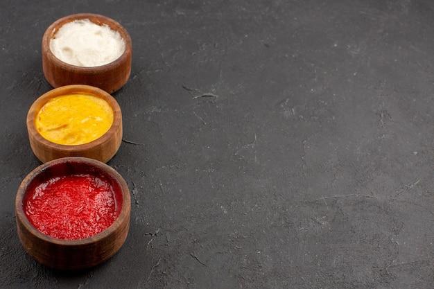 Vista frontal de ketchup e mostarda com maionese dentro de pequenos potes no espaço escuro