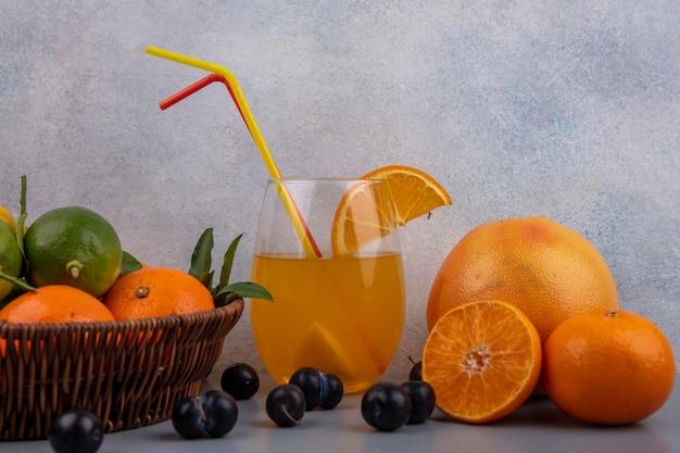 Vista frontal de laranjas com limões e limas em uma cesta com suco de laranja em um copo com morangos em um fundo cinza
