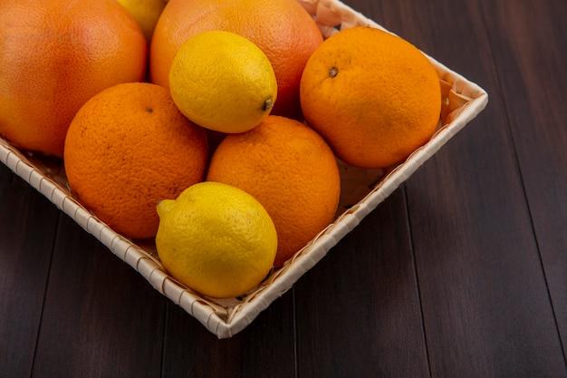 Vista frontal de laranjas em uma cesta com limões e toranjas em um fundo de madeira