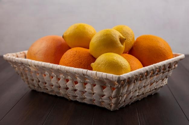 Vista frontal de laranjas em uma cesta com limões e toranjas