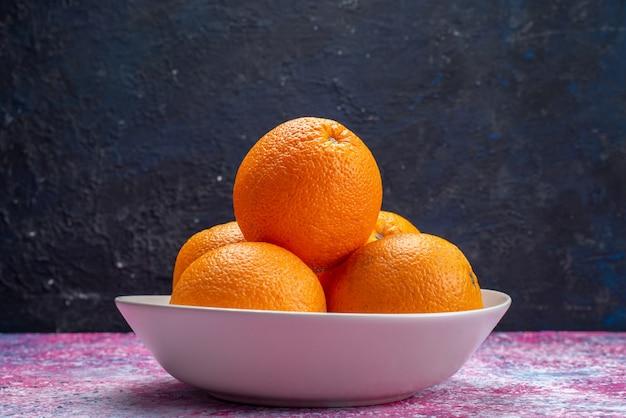 Vista frontal de laranjas frescas dentro de uma placa branca no escuro