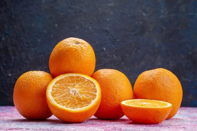 Vista frontal de laranjas frescas no escuro