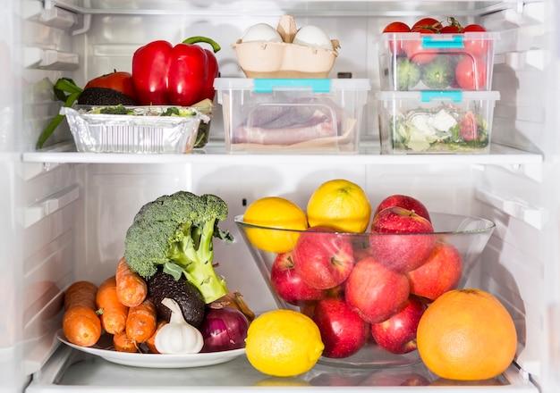 Vista frontal de legumes e refeições na geladeira