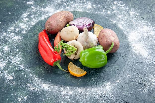 Vista frontal de legumes frescos alho pimenta cebola e batatas na salada madura azul escuro comida planta refeição de vegetais