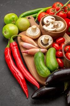 Vista frontal de legumes frescos com cogumelos na mesa de cor escura salada madura fresca