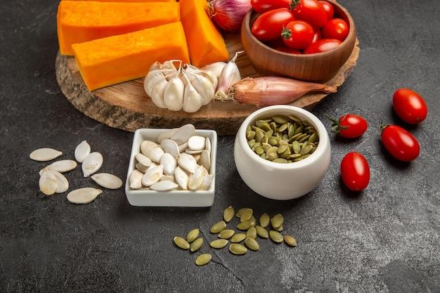 Vista frontal de legumes frescos com fatias de abóbora e alho na cor de semente de fundo cinza salada madura fresca