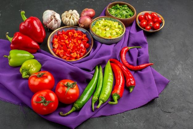 Vista frontal de legumes frescos com pimenta e alho em fundo escuro