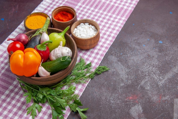 Vista frontal de legumes frescos com temperos em fundo escuro salada madura de alimentos saudáveis