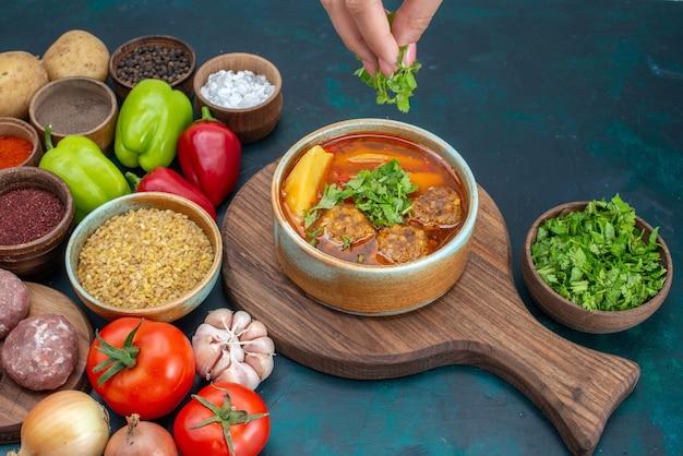 Vista frontal de legumes frescos com temperos, sopa de carne e verduras, em uma mesa azul-escura com pratos de comida de vegetais, verduras