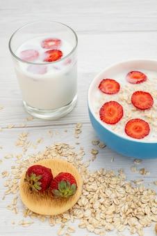 Vista frontal de leite com aveia dentro da placa com morangos junto com copo de leite em branco