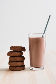 Vista frontal de leite com chocolate em copo com palha e bolachas