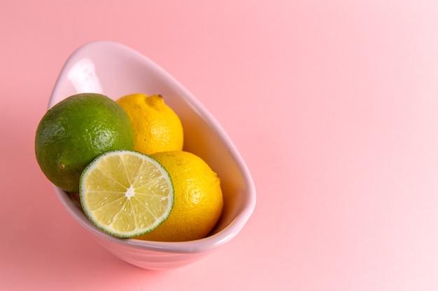 Vista frontal de limão fresco com limão fatiado dentro do prato na parede rosa