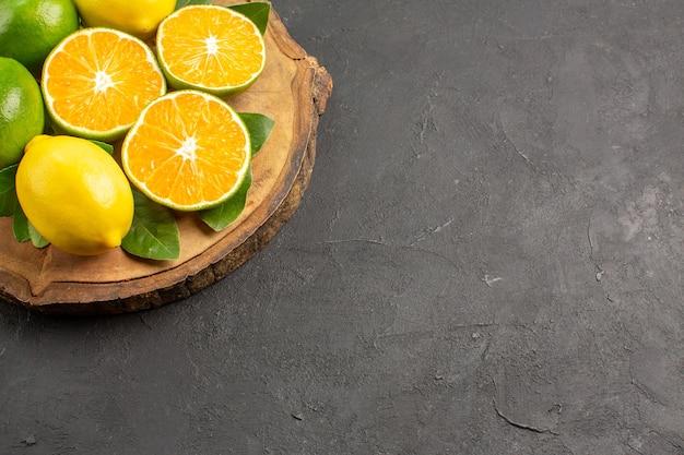 Vista frontal de limões azedos frescos em piso escuro com lima e frutas cítricas