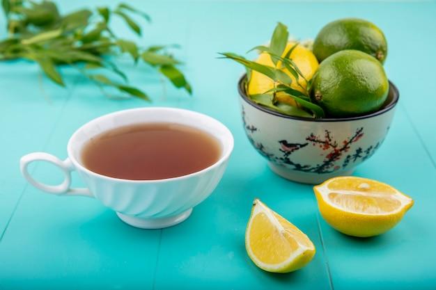 Vista frontal de limões em uma tigela com uma xícara de chá fatias de limão na superfície azul