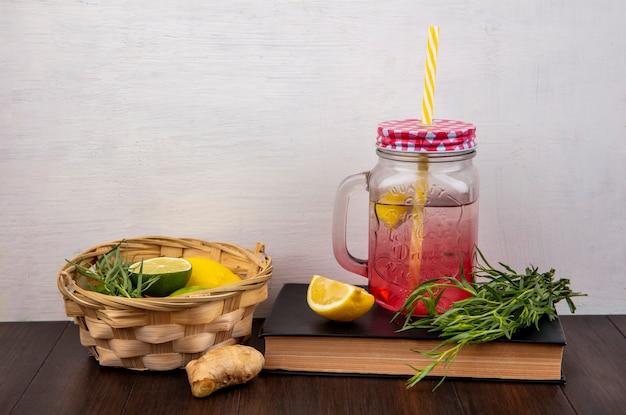 Vista frontal de limões frescos em um balde com estragão com suco de limão em uma jarra de vidro na superfície branca