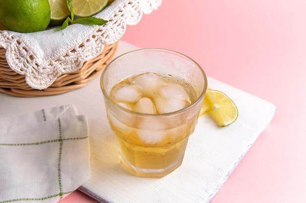 Vista frontal de limonada fresca com gelo dentro do copo e limões frescos na mesa rosa