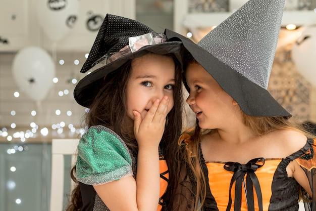 Vista frontal de lindas garotinhas com fantasia de bruxa