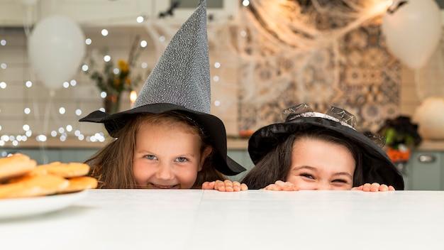Vista frontal de lindas garotinhas com fantasias de halloween