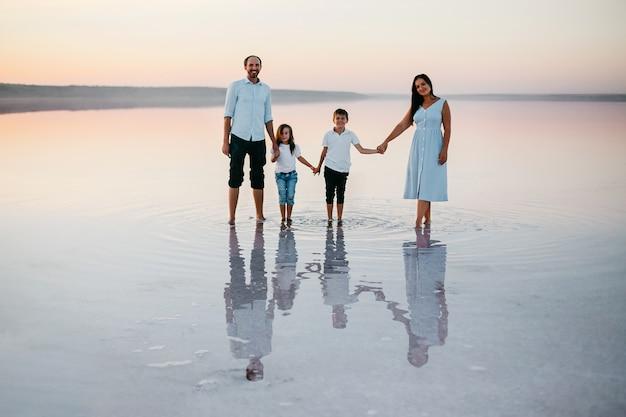 Vista frontal de lindos pais jovens, sua linda filha e filho de mãos dadas, caminhando na praia