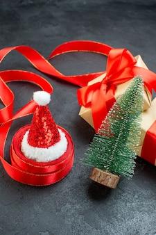Vista frontal de lindos presentes com fita vermelha e árvore de natal, chapéu de papai noel em uma mesa escura