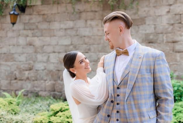 Vista frontal de lindos recém-casados se olhando e sorrindo na rua