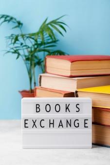 Vista frontal de livros empilhados com planta e caixa de luz