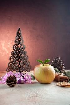 Vista frontal de maçã fresca madura com brinquedos e pequena árvore de natal na cor da foto da árvore de suco suave