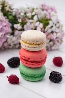 Vista frontal de macarons coloridos com amoras e framboesas em uma superfície branca