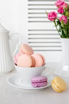 Vista frontal de macarons em copo com rosas