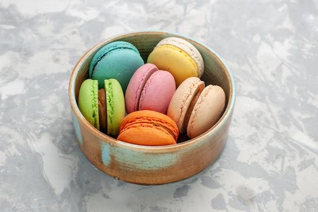 Vista frontal de macarons franceses coloridos deliciosos bolinhos na superfície branca