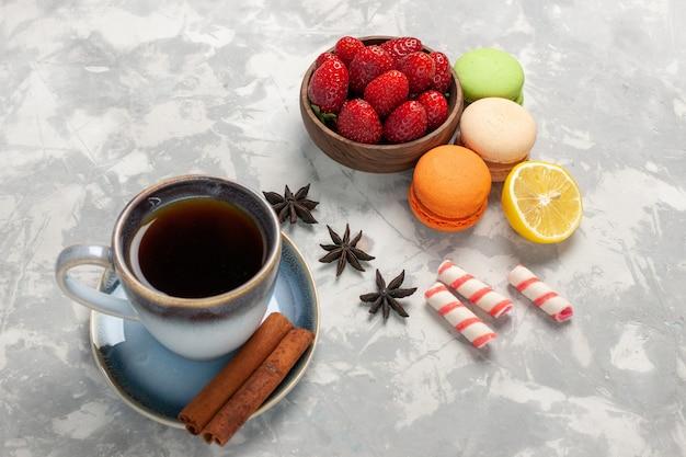 Vista frontal de macarons franceses com chá de canela e morangos frescos em uma superfície branca de frutas, bolo de frutas vermelhas, biscoito doce