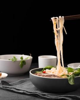 Vista frontal de macarrão cozido em tigela com hortelã