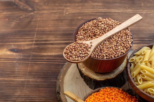 Vista frontal de macarrão cru com trigo sarraceno e lentilhas na superfície marrom