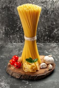 Vista frontal de macarrão longo italiano com tomate vermelho e alho em uma refeição fotográfica de cozinha de massa de cor cinza claro
