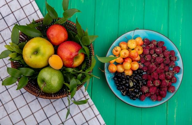 Vista frontal de maçãs coloridas em uma cesta com cerejas brancas, framboesas e groselhas em um prato sobre uma superfície verde